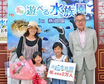 2万人目となった吉田蛍さん(右から2人目)=17日、湯梨浜町の中国庭園燕趙園
