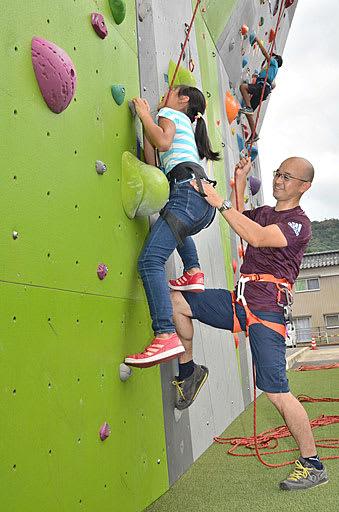 安井さん(右)の指導でクライミングに挑戦する児童ら