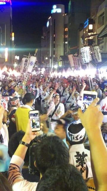 大勢の見物客で騒然とする中、演舞場外で「総踊り」を強行する阿波おどり振興協会の踊り子ら=13日午後10時半ごろ、徳島市
