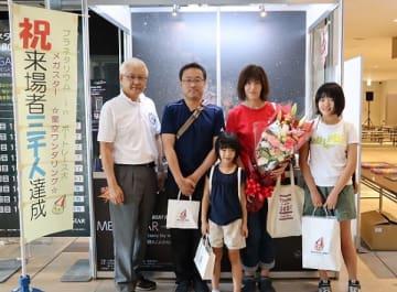 3000人目の来場者となり、小川局長(左)から記念品が贈られた金子さん一家=大村ボートレース場