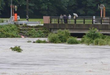 大雨で増水した相内川。市が避難指示を出したものの、実際に避難する住民は少なかった=16日午後4時半ごろ、五所川原市相内