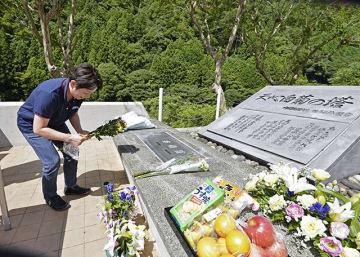 飛騨川バス転落事故から50年の慰霊法要を前に、花を手向ける遺族の女性=18日午前10時26分、加茂郡白川町河岐、天心白菊の塔