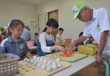 子どもたちにゲームを教える小林正義さん=東海村村松