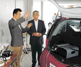 電気自動車の電源を利用していれたコーヒーを飲みながら、吉沢代表理事(左)の説明を聞く亀山市長