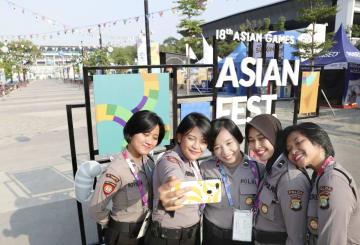 アジア大会の開会式が行われるブンカルノ競技場(奥)の前で記念撮影する女性たち=18日、ジャカルタ(共同)
