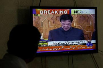 18日、パキスタン南部カラチで、イムラン・カーン首相の就任宣誓をテレビで見る男性(ロイター=共同)