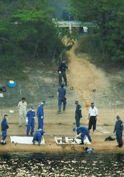 遺体発見現場の周辺を調べる捜査員=11日午後、加古川市平荘町中山