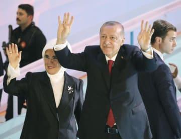 トルコの首都アンカラでの与党大会で、党員に手を振るエルドアン大統領(中央)=18日(共同)