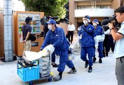 20歳の男の自宅マンションから出る兵庫県警の捜査員=18日午後5時13分、大阪市西区