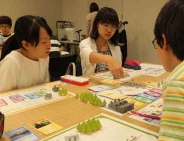 ボードゲームを通じて環境問題を学ぶ参加者=横浜市中区の日本新聞博物館