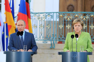 会談前に記者会見するロシアのプーチン大統領(左)とドイツのメルケル首相=18日、ベルリン近郊(ゲッティ=共同)