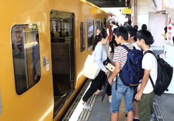 大勢の利用客が列車に乗り込んだ瀬野駅のホーム=18日午前8時6分