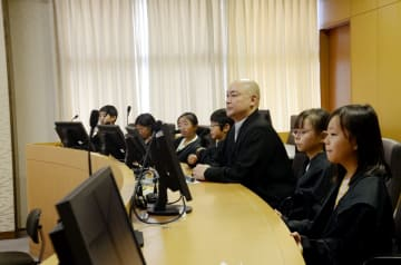 裁判劇の判決言い渡しでは、法服をまとった小学生たちが並んだ。中央は県弁護士会の奥田律雄会長=佐賀市の佐賀地裁