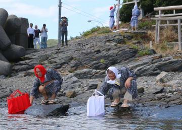 航海の安全を祈り、紅白の小舟の模型を海に浮かべる豆酘地区の住民=対馬市