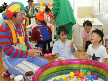 クラウン姿で子どもたちとカラーボールをすくうゲームをする佐藤慎二郎さん(左端)=大分市の県立病院