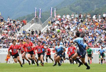 大入りの観客席を背に熱戦を繰り広げる釜石シーウェイブスRFCとヤマハ発動機の選手=19日午後2時47分、釜石市・釜石鵜住居復興スタジアム