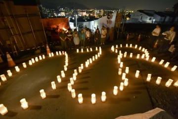 「820」の形に並べられた灯籠の前で黙とうする人たち=20日午前4時12分、広島市安佐南区