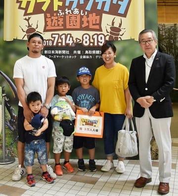 節目の入場者となり、吉岡社長(右)から記念品が贈られた浜本さん一家=19日、境港市の夢みなとタワー