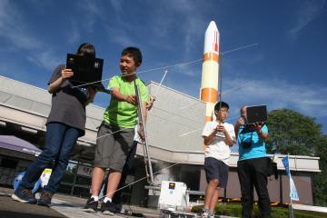 人工衛星の方角にアンテナを向けて電波を受信する中学生ら=つくば市吾妻