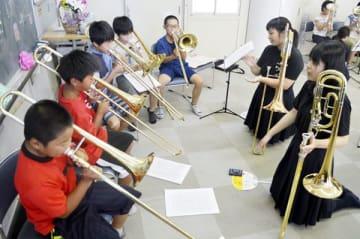 児童にトロンボーンの演奏方法を教える川島高の生徒(右側の2人)=吉野川市鴨島町の牛島小