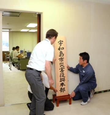 宇和島市災害復興本部の看板を設置する岡原文彰市長(右)ら=20日午前、市役所
