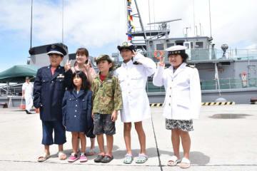 掃海艇「うくしま」を背景に、自衛隊の制服を着用し記念写真を撮る家族連れ