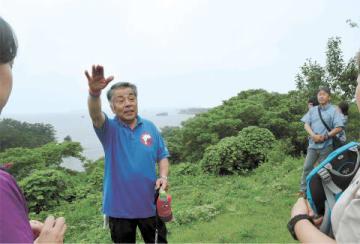 オルレ奥松島コースになる稲ケ崎公園で地形や浜の生活を説明する木島さん