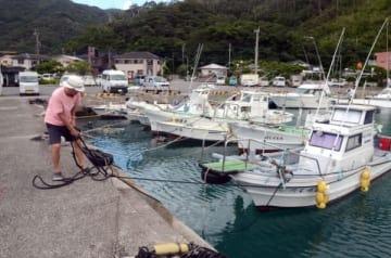 ロープで岸壁に船を固定する漁業関係者=奄美市の大熊漁港
