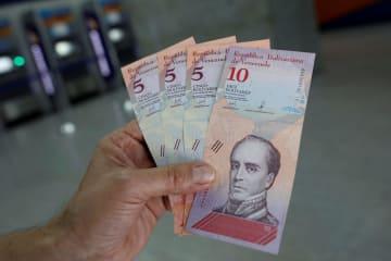 20日、南米ベネズエラの首都カラカスで、現金自動預払機(ATM)から引き出された新通貨ボリバル・ソベラノの紙幣(ロイター=共同)