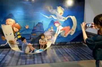 「ゲゲゲの鬼太郎 トリックアートの館」で撮影を楽しむ家族連れ=湯前町