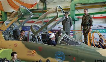 21日、テヘランで開かれた国産戦闘機の公開式典で操縦席に座るイランのロウハニ大統領(手前中央)(イラン大統領府提供・共同)