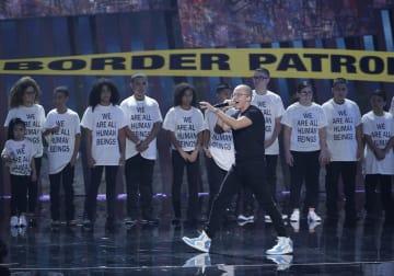 「私たちはみんな人間です」と書かれたTシャツを着た子どもたちと共に、MTVの音楽イベントに出演したロジックさん=20日、ニューヨーク(UPI=共同)