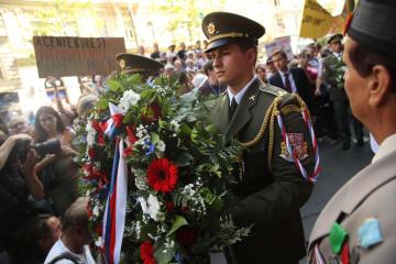 21日、チェコ・ラジオ前での式典で、市民の前で花輪を運ぶ護衛兵=プラハ(ゲッティ=共同)