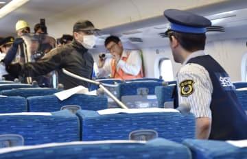 JR東海が新幹線車内で行った不審者対応訓練で、凶器を持った不審者(奥)に対応する警備員(手前)ら=22日午後、静岡県三島市
