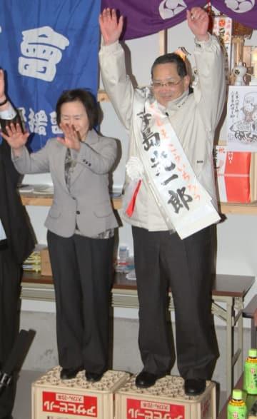 2015年4月、8回連続で無投票となった北海道乙部町長選で9選を決め、万歳する現職の寺島光一郎氏(右)