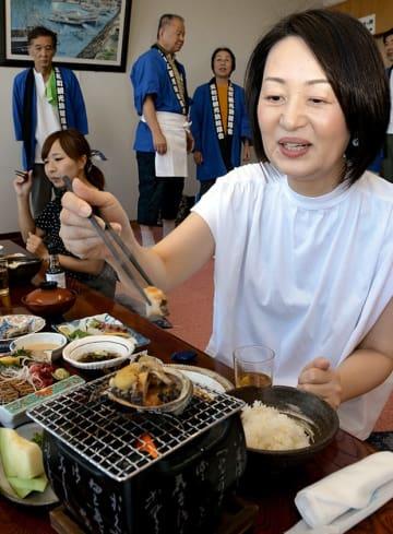 「アワビまつり」で提供されるアワビの姿焼きにはしを伸ばす女性=天草市