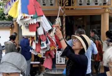 六地蔵めぐりで、綱にお幡をくくりつける参拝者(22日午前9時55分、京都市北区・上善寺)
