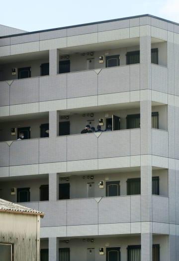 原雄太さんが死亡していた愛知県あま市のマンション。中央は現場検証する捜査員=22日
