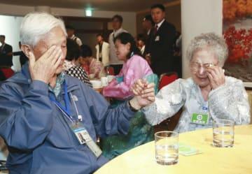 北朝鮮・金剛山での南北離散家族再会事業で、北朝鮮の家族(右)との別れを惜しみ涙ぐむ韓国の男性=22日(韓国記者団・共同)