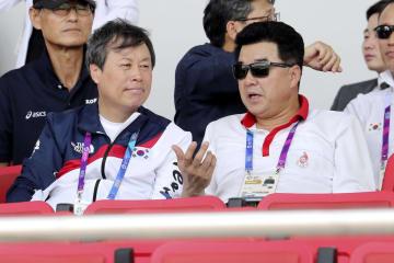 南北合同チームのボート競技を観戦する韓国の都鍾煥・文化体育観光相(左)と北朝鮮の金日国体育相=22日、パレンバン(聯合=共同)
