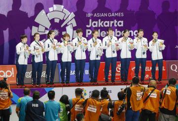 ジャカルタ・アジア大会のバドミントン女子団体で優勝し、表彰式で金メダルを手に笑顔の日本チーム=22日、ジャカルタ(共同)