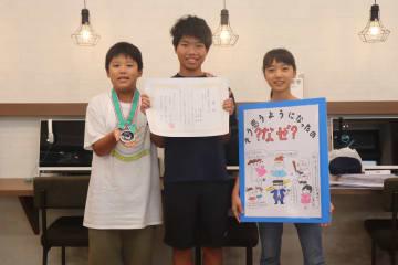 表彰状やメダル、自作のポスターを手にする(左から)齋藤君、窄さん、長谷川さん=長崎市平和町、真未来塾