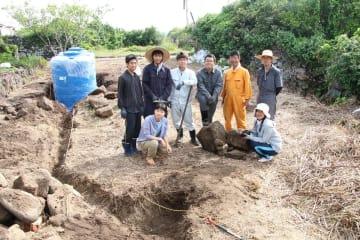 雨水を貯めるタンク(左奥)の設置や、配管を埋めるための溝を掘る作業などに取り組む学生ら=五島市、赤島