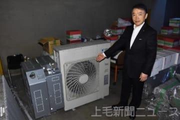 古い空調機器を示す吉田社長。業務用の場合、1トンを超える設備もある