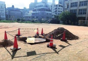 運動場の中央付近で見つかった不発弾。運動場全体を立ち入り禁止にしている(那覇市提供)