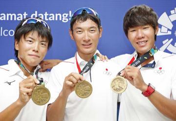 銅メダルを手に笑顔の男子シングルスカル荒川(中央)と、男子かじなしペアの大塚(左)、高野組=パレンバン(共同)