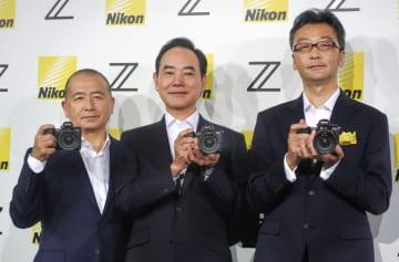 ミラーレス一眼カメラの新機種を手にするニコンの牛田一雄社長(中央)ら=23日、東京都品川区