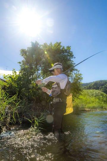 今年一番の暑さの中、アユ釣りを楽しむ釣り人=23日、三戸町