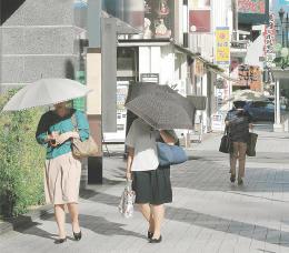 顔が隠れるほど日傘を深く傾け、強い日差しを逃れる女性たち=23日午後3時30分ごろ、山形市香澄町1丁目