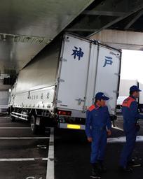 海水で約7メートルほど流され、神戸大橋の橋桁にぶつかったトラック=24日午前9時50分、神戸市中央区新港町